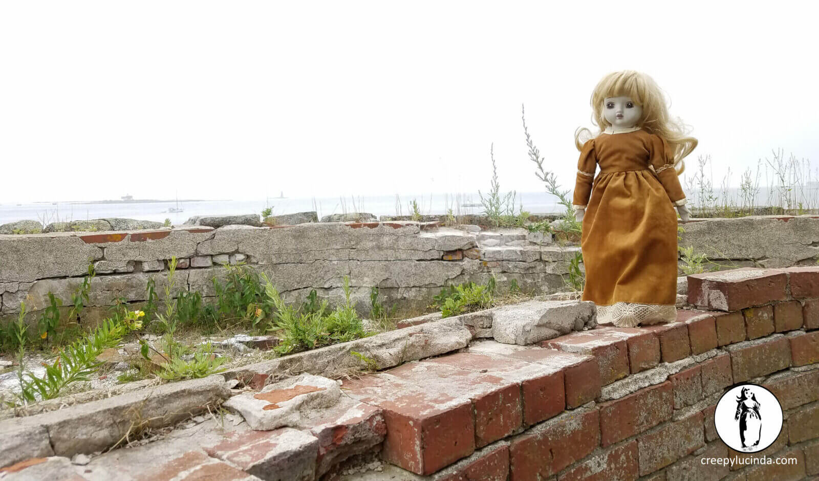 Creepy doll standing on a brick wall