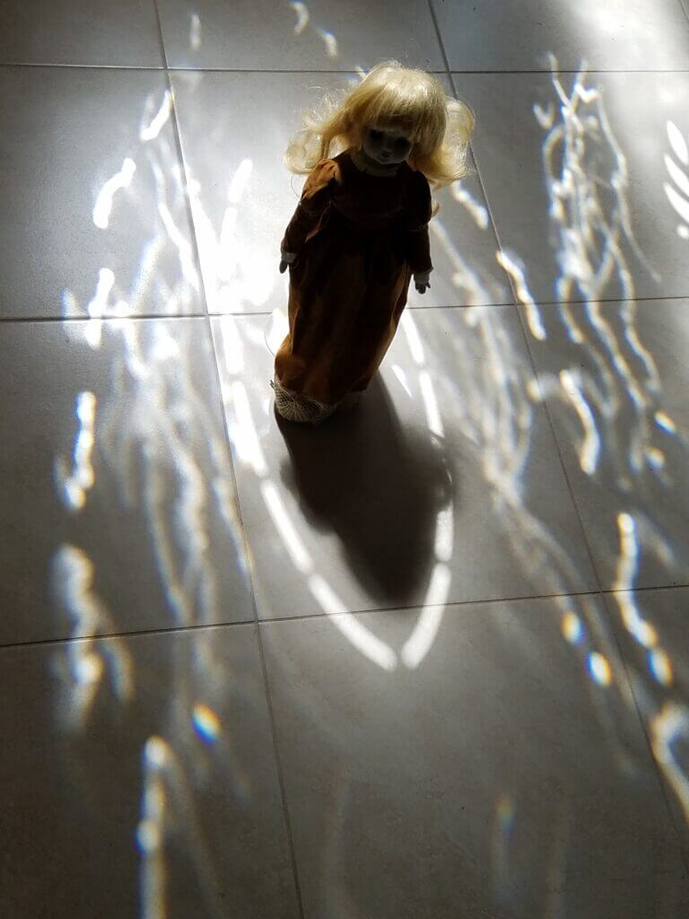 Silhouette of a creepy doll in light and shadow