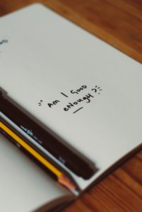 "A journal with the words ""am I good enough?"" written in marker"