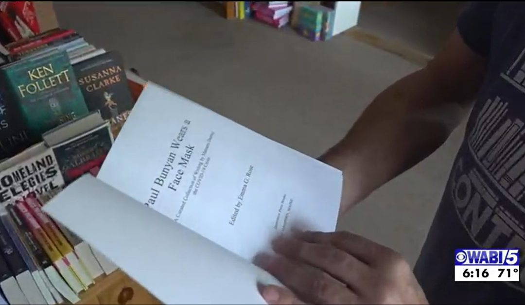 Screenshot from TV newscast, hands hold a copy of Paul Bunyan Wears a Face Mask open to the title page.