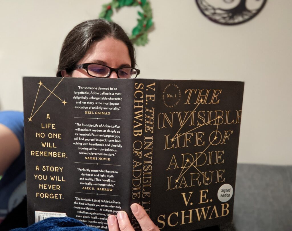A woman reads The Invisible Life of Addie LaRue by V.E. Schwab